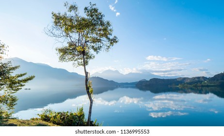 Beautiful landscape view of mountain and lake with reflection in the morning under blue sky and white cloud at Sun Moon Lake, Nantou, Taiwan
