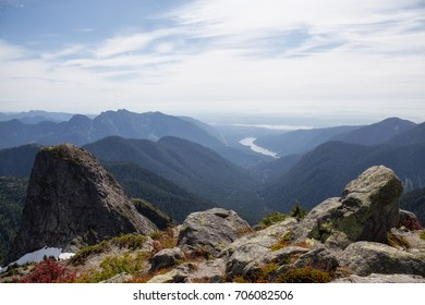 Beautiful landscape view of mountain top, valley, and Capilano Lake. Picture taken at the top of Lions Peak in Lions Bay, North of Vancouver, British Columbia, Canada.