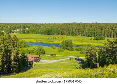 Beautiful landscape view on summer day. Private wooden houses between green forest trees. Small river along asphalt road.