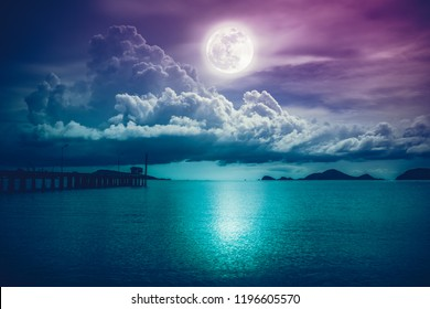 Beautiful landscape view of the sea. Colorful sky with clouds and bright full moon on seascape to night. Serenity nature background, outdoor at nighttime. The moon taken with my own camera.