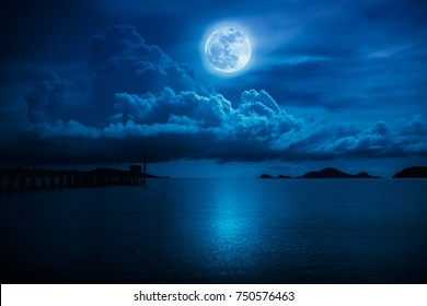 Beautiful landscape view of the sea. Colorful blue sky with clouds and bright full moon on seascape to night. Serenity nature background, outdoor at nighttime. The moon taken with my own camera.