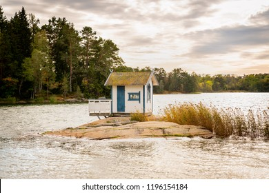 Beautiful landscape view of a small bath hut cottage on a rock in a lake surrounded by trees and reed.