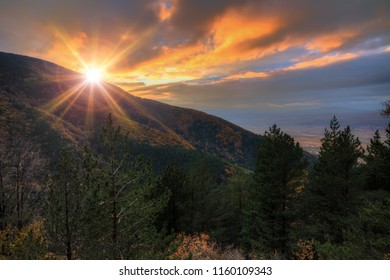 Beautiful landscape view at sunset of the mountains of the Rila Nature Park in Bulgaria with vibrant autumn colors in the forest