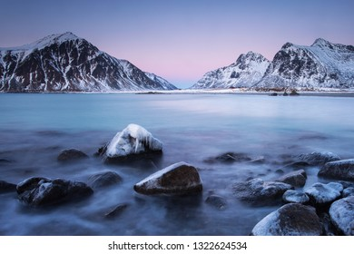 Beautiful landscape view with water in motion and mountain in background. Lofoten, Norway