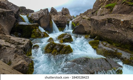 Beautiful landscape with a waterfall on a small mountain river in Iceland.  Clear Water flows in a stormy stream among stones and rocks covered with moss