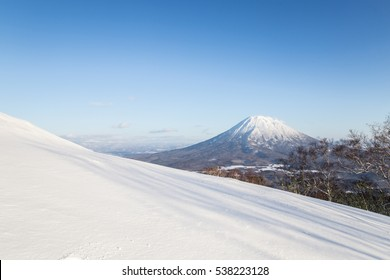 Beautiful landscape of white snow hill on front of Mt.Yotei, the active stratovolcano in, Hokkaido, Japan. The winter scene under blue sky from Ski-resort in Niseko Annupuri area