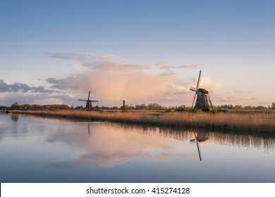 Beautiful landscape with windmills and majestic sky reflection in water