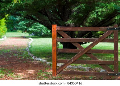 Beautiful landscape with a wooden fence at the entrance to a green garden