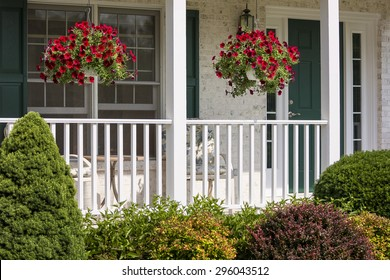 A beautiful landscaped American front porch with white railings and hanging baskets with red flowers.