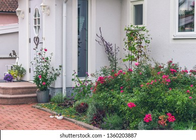 Beautiful landscaped front yard of a white house with flowers, rose bushes, different garden decoration and red tiled pathway. Various, diverse, varied garden decor in front of porch with staircase.