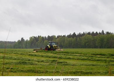 Beautiful lansdscape with haymaking is mowing the grass on a green field