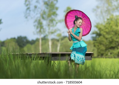 Beautiful Lao young woman wearing tradition dress sitting on wooden bridge and holding umbrella in green rice field