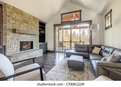 Joli grand plafond voûté clair murs blancs salon intérieur avec canapé en pierre et cuir et bois dur gris foncé.