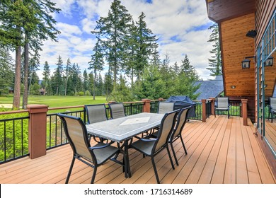 Beautiful large cabin home  with large wooden deck and chairs with table overlooking golf course.