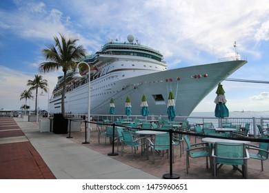 beautiful large cruise ship, big white passenger boat, luxury modern cruise ship at moorage in port next to cafe