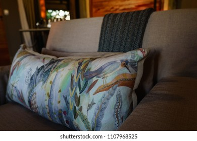Beautiful large cushion with bird and flower print on armchair.