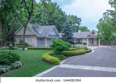 A beautiful large custom bungalow home with a grey brick and stone exterior and a 3 car garage, on a quite town street with a winding circular paved driveway and lush trees, gardens and lawn.