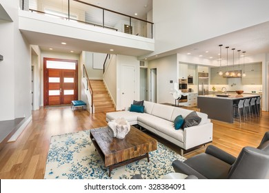 Beautiful and large living room interior with hardwood floors and vaulted ceiling in new luxury home. View of Kitchen, entryway, and second story loft style area