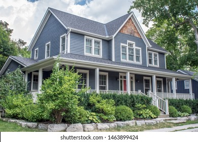 A beautiful large modern custom executive residential house with grey siding and gray shingles and white trim, large over sized windows, lush gardens and green lawn.