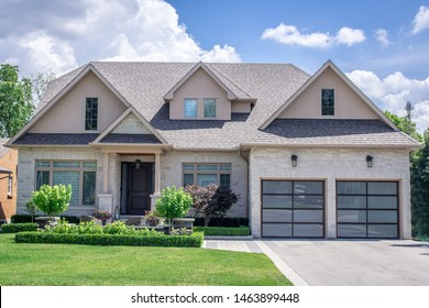 A beautiful large modern custom executive residential house with grey stone and brick, with gray shingles and grey trim, patterned interlock walkway and driveway, and double glass garage doors.