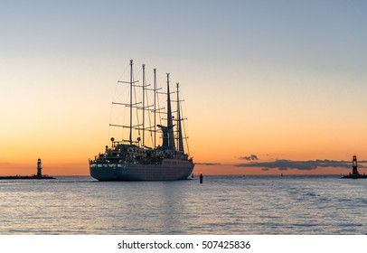 Beautiful large sail ship is leaving the marina. It is moving into the sunset over the Baltic Sea. Image taken as a long shutter pic. The ship has five masts to sail.