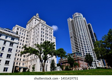 Beautiful large white buildings in downtown Milwaukee contrasting against a blue sky as seen from Juneau Park