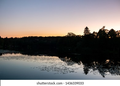 Beautiful late summer night sunset with calm water reflections and dark trees against clear sky.