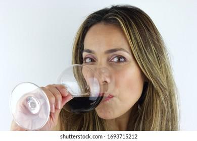 Beautiful Latin American Woman drinking a glass of red Wine