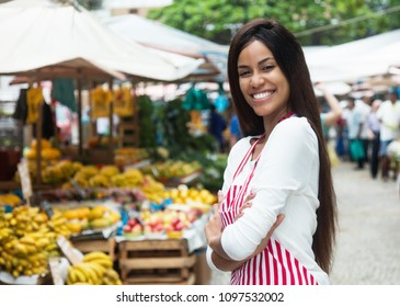 Beautiful latin american woman selling fruits outdoors at farmers market
