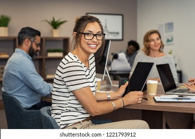 Beautiful latin businesswoman looking at camera and smiling while working in office. Cheerful young woman wearing spectacles and holding digital tablet. Creative girl working with colleagues.