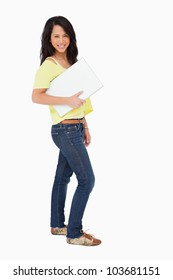 Beautiful Latin student holding a laptop against white background