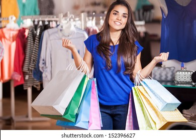 Beautiful Latin woman carrying so many shopping bags in a clothing store