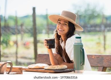 beautiful latin woman with hat drinking yerba mate