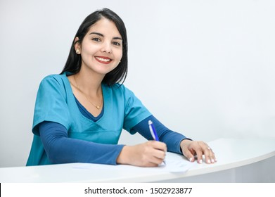 Beautiful latin woman medical receptionist smiling to the camera and writing notes. Background, copy space