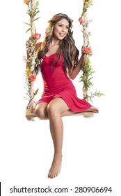 Beautiful latin woman on swing on white background
