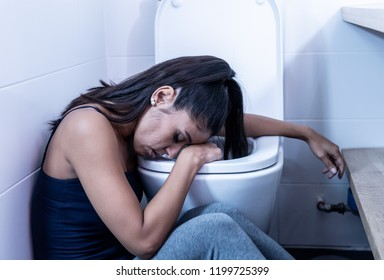 Beautiful latin woman sitting in the bathroom suffering from anorexia bulimia feeling desperate sad and guilty in eating disorders and ill pregnancy concept.