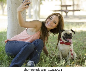 Beautiful latin woman taking a picture with her dog at the park