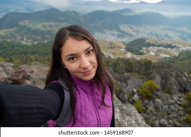 Beautiful latin woman taking a selfie on top of the mountain with the small town behind her- Hispanic traveler