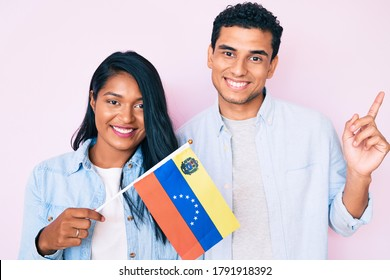 Beautiful latin young couple holding venezuelan flag smiling happy pointing with hand and finger to the side