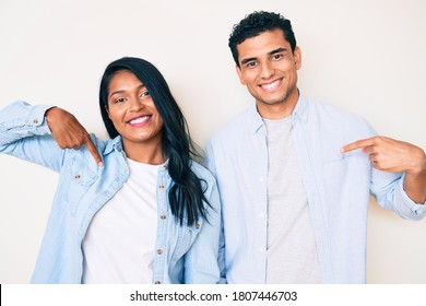 Beautiful latin young couple wearing casual clothes looking confident with smile on face, pointing oneself with fingers proud and happy.