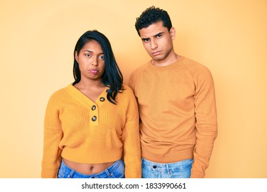 Beautiful latin young couple wearing casual clothes together depressed and worry for distress, crying angry and afraid. sad expression.