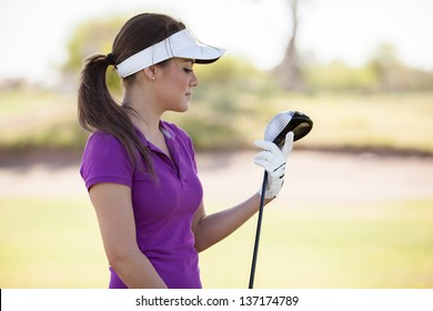 Beautiful Latin young golfer holding a golf club