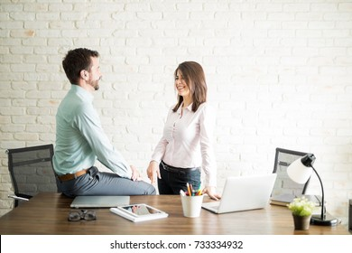 Beautiful Latin young woman having an office fling with a colleague and smiling
