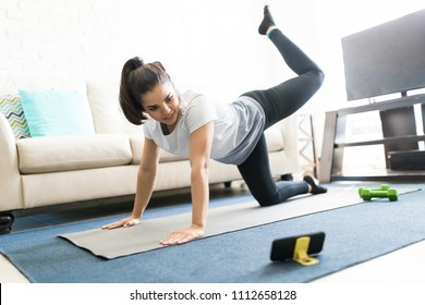 Beautiful latin young woman repeating exercises while watching online exercise session on her smart phone at home