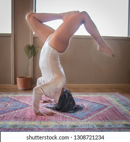Beautiful latina girl doing difficult yoga poses on carpet