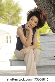 Beautiful Latina model with curly hair sitting in the shade of a tree on sunny day.