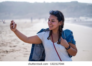 Beautiful latina taking a selfie on vacation on the beach