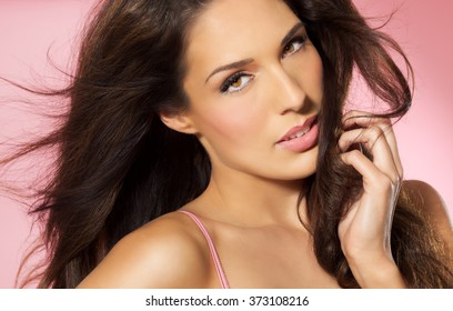 Beautiful Latina woman with long dark hair over warm pink background in studio. Fashion and beauty concept.