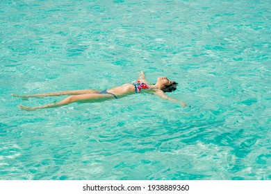 Beautiful Latina woman in a swimsuit with flowers floating in the blue sea in Cozumel Mexico.