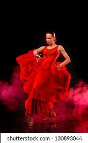 Beautiful Latino dancer in action. Over dark smoky background
